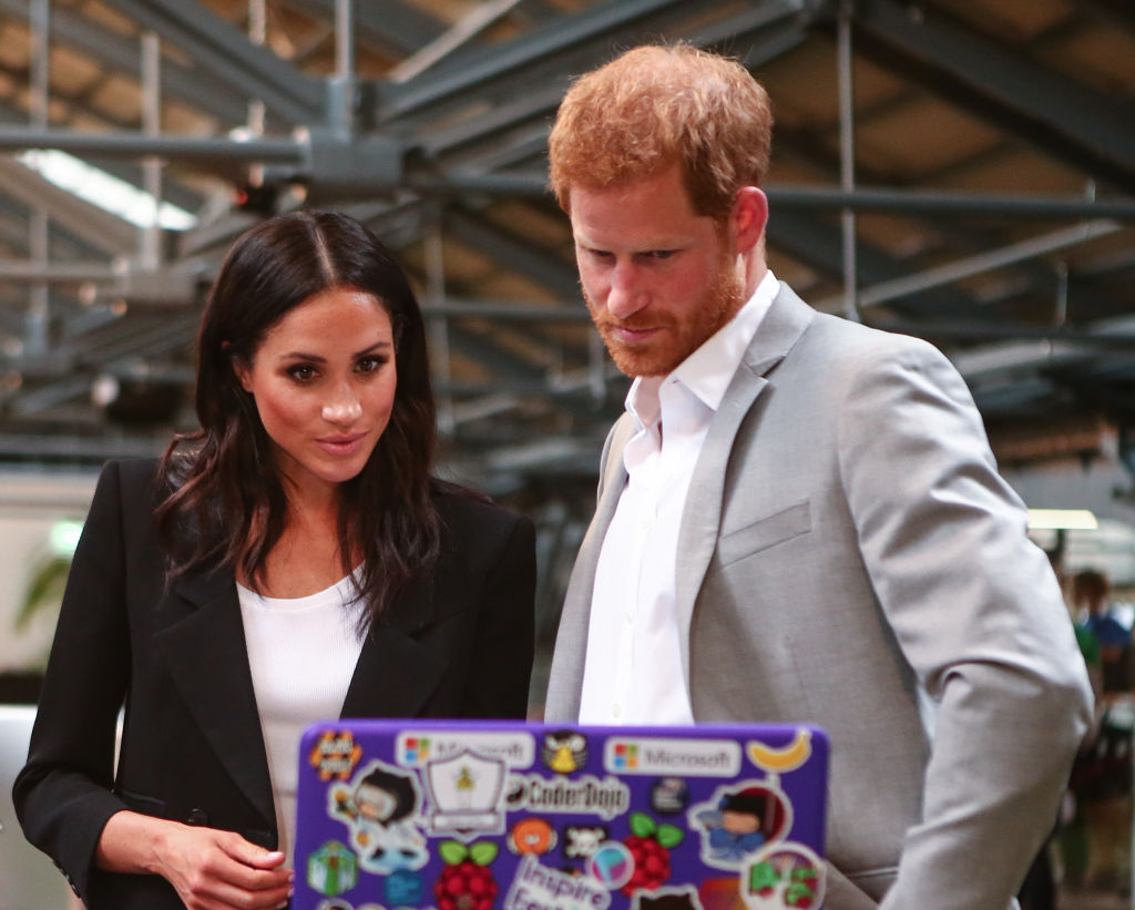 Prince Harry and Meghan Markle look at a computer