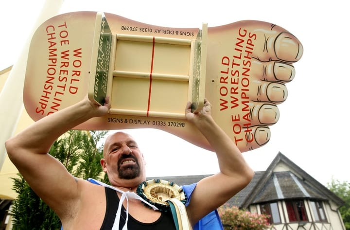 Toe Wrestling Champion holding trophy shaped like a foot