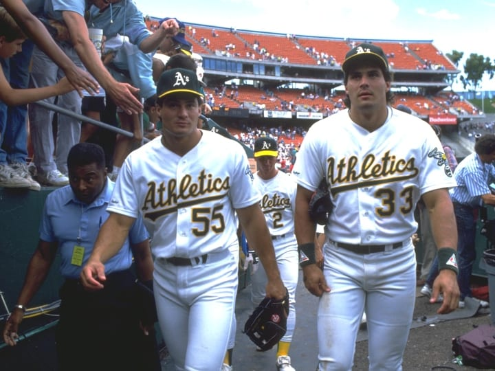 1990: THE CANSECO TWINS, OZZIE, LEFT, AND JOSE, WALK OFF THE FIELD AFTER THE OAKLAND A''S 1990 GAME SEASON AT THE OAKLAND COLISEUM IN OAKLAND, CALIFORNIA. MANDATORY CREDIT: OTTO GREULE/ALLSPORT.