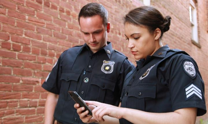 Two police officers looking at a phone