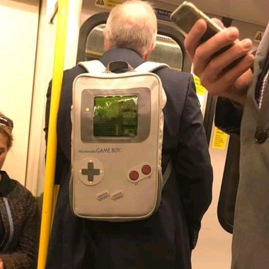 Game man, game boy backpack, on the train