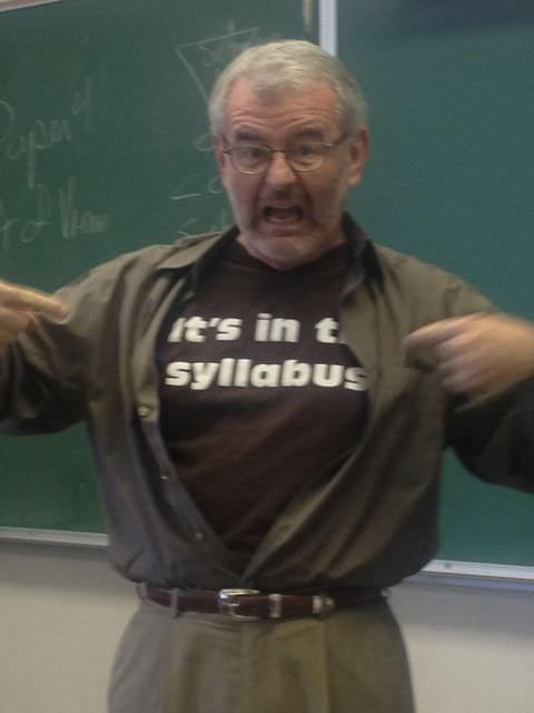 """Professor standing in front of chalkboard points to shirt reading """"It's in the syllabus"""""""