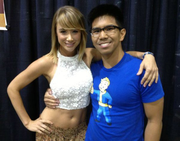 Man poses for picture with woman in a crop-top. Man is wearing shirt with cartoon seemingly touching woman