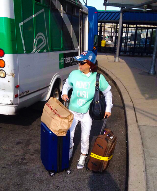 Woman exits bus with luggage wearing ironic shirt