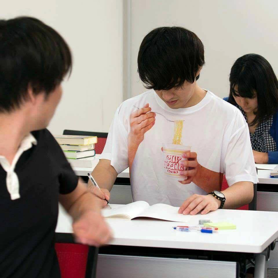 Man wearing shirt that makes it appear as if he is eating cup-o-noodles